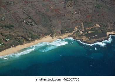 Aerial of Northwest coast of Molokai with waves crashing into Sandy Beach and surrounding area of island with roads, largely undeveloped. April 2016.