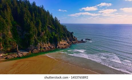 Aerial of ocean beach cove, rocky shoreline, trees, waves, sky, sun