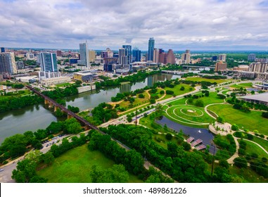 Aerial Over Austin Texas spring time colors with Railroad Tracks crossing Lady bird lake at Zilker Park and Auditorium Shores with Skyline Cityscape and downtown in the background North of the River