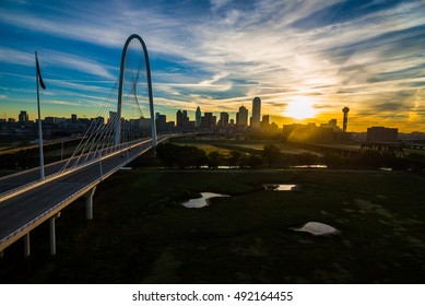 Aerial over Margaret Hunt Hill Bridge with Texas flag on a calm morning as the sunrises over the downtown Dallas Texas Skyline Cityscape over Trinity park an Amazing City view