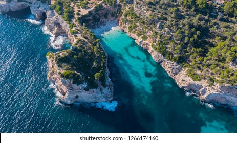Aerial overhead drone view of the beautiful Calo des Moro, Mallorca showing turquoise water and rocky coastline with a sheltered empty virgin beach with white sands.