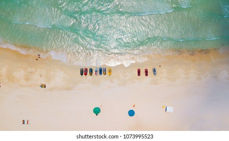 Aerial : Overhead  of people enjoying the summer at sand  beach ,waves breaking against the coast line