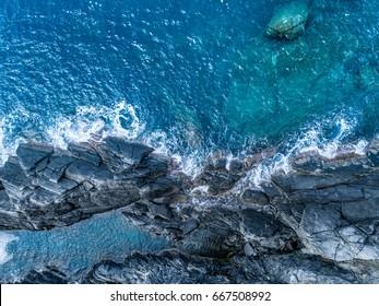 aerial overhead top view of ocean mediterranean sea waves reaching and crashing on rocky shore beach, near travel landmark destination Cinque terre National Park, Liguria, Italy. Sunny weather.