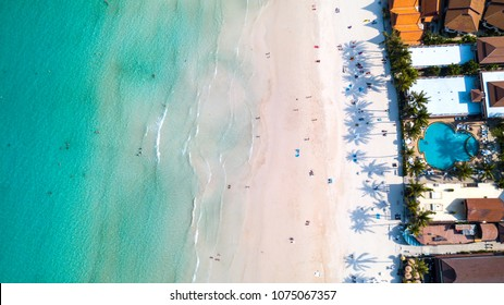 Aerial overhead view of green foaming waves crushing against the sandy coast line, people enjoy summer  near resorts and hotel line