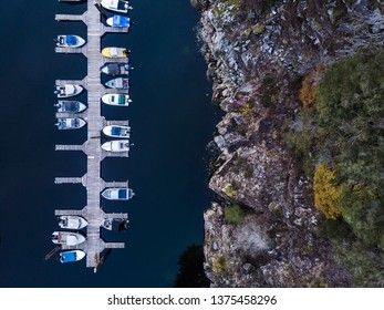 Aerial overhead view of a wooden boat dock next to a rocky seaside cliff.
