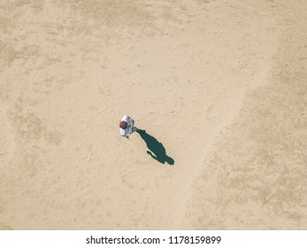 aerial overhead view of young man walking alone in the sandy sea beach, abstract concept background