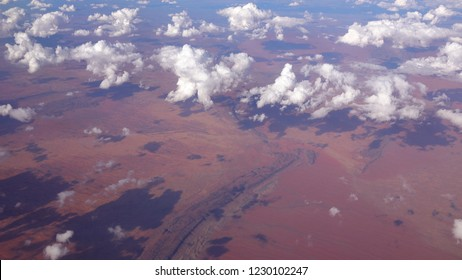 AERIAL: Overlook from airplane on Great Victoria Desert above white puffy clouds. View of stunning vast arid soil landscape scenery and deserted area with red sandy sandhills and dry plains