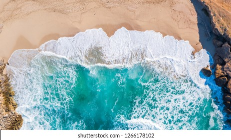 Aerial overview of huge waves crashing into the shore and rocks at Cala Mitjana, Mallorca, overview shot showing the dynamic coastline of the turquoise waters of Mallorca spain.