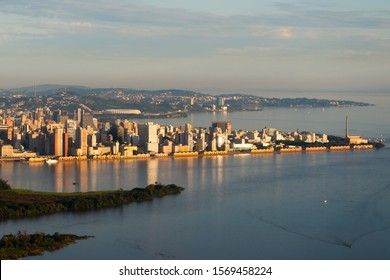 Aerial overview of Porto Alegre, Brazil. Beautiful sunset light illuminating the downtown skyline with reflection on Guaiba River water. Administrative building and football stadium visible.