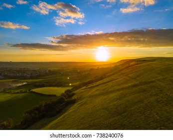 Aerial overview sunset with green field hills, clouds, blue sky and sea england UK