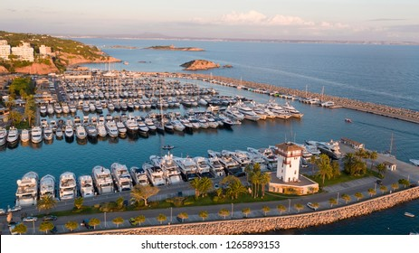 Aerial overview of yacht marina in Puerto Portals, Mallorca at sunset hour, showing yachts sheltered on the beautiful Mediterranean coastline.