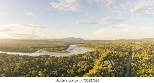 Aerial panorama of an Amazonian highway in Ecuador at dusk with Rio Napo and Galeras mountain in the background.  Roads bring colonization and destruction of the rainforest to the Amazon Basin.
