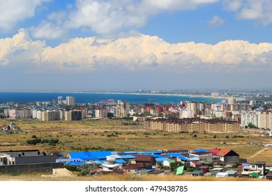 Aerial panorama of Anapa resort city, Russia. Summer day under blue cloudy sky. View from mountain. New buildings, construction cranes and Black Sea water.