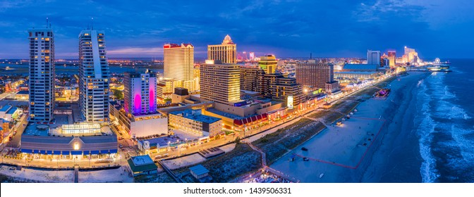 Aerial panorama of Atlantic city along the boardwalk at dusk. In the 1980s, Atlantic City achieved nationwide attention as a gambling resort and currently has nine large casinos.