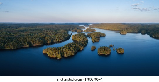 Aerial panorama of beautiful blue lake, islands and green summer forest in Finland. Blue sky. Top view. Summer sunset lanscape.