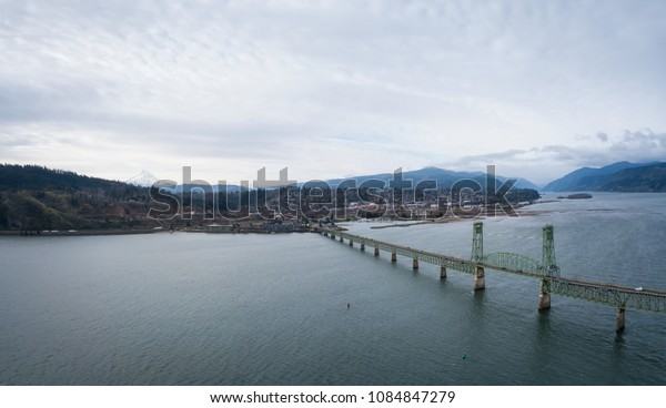 Aerial panorama of a bridge going over Columbian River between Oregon and Washington during a winter day.