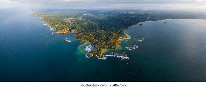 Aerial panorama of the cape of the town of Weligama with fisherman boats, beaches and waves breaking on the reef. Sri Lanka