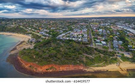 Aerial panorama of coastline, beaches and Australian suburban area at sunset. Mornington Peninsula, Melbourne, Victoria, Australia