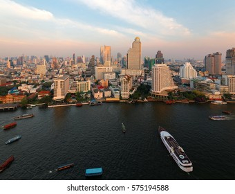 Aerial panorama of downtown Bangkok, the capital city of Thailand, with a beautiful urban skyline of modern skyscrapers and busy traffic of ferries & tour boats on Chao Phraya River under sunset sky