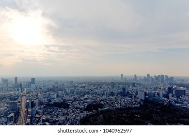 Aerial panorama of Downtown Tokyo at sunset, with an expressway running thru Shibuya area & high-rise office towers clustering in Shinjuku District in hazy dusk~City skyline of Tokyo in misty twilight