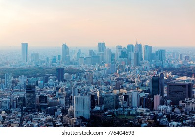 Aerial panorama of Downtown Tokyo at sunset, with high-rise office towers clustering in Shinjuku District & an urban park among crowded buildings in hazy dusk ~ City skyline of Tokyo in misty twilight