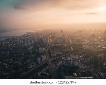 Aerial panorama of dramatic sunset above evening Voronezh city in haze or fog, bird eye view of urban downtown architecture in twilight, toned