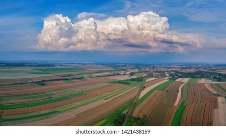 Aerial panorama of fields under blue sky and big white cloud