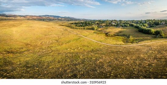 aerial panorama of foothills prairie along Front Range of Rocky Mountains near Fort Collins, Colorado, summer scenery lit by sunrise - - Cathy Fromme Prairie Natural Area with a bike trail
