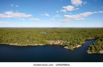 Aerial panorama of a fresh water lake surrounded by rugged rocky cliffs and endless green boreal coniferous forest. Northern Ontario, Canada.
