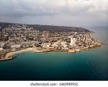 Aerial panorama of Haifa from flying drone - the third largest city of of Israel. Beautiful view of coast and seaside city on the hill. Sea shore, town, blue water and skyscape. Cityscape