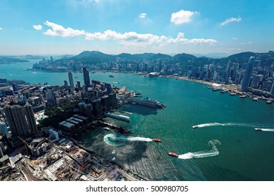 Aerial panorama of Hong Kong & Kowloon (Tsim Sha Tsui) on a sunny day with view of city skyline of crowded skyscrapers by Victoria Harbour & ships across busy seaport ~ Beautiful cityscape of Hongkong