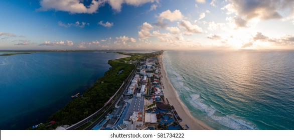 Aerial panorama of Hotel Row in Cancun, Mexico featuring the major hotels and resorts with white sandy beaches and blue ocean during a morning sunrise
