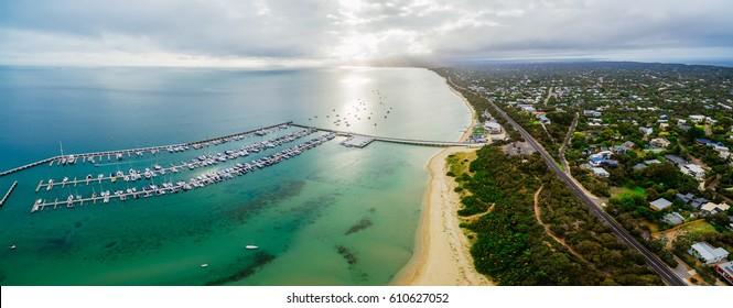 Aerial panorama of land and sea. Long pier and yachts moored at marina near the beach