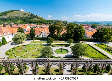 """Aerial panorama of Mikulov city, czech republic. The tower of St Wenceslas in foreground. """"Svaty kopec"""" hill with St Sebastian chapel in background. Look to town roofs, summer day."""