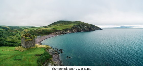 Aerial panorama of the Minard Castle situated on the rocky beach of the Dingle Peninsula with views across the Irish Sea in Kerry county, Ireland.
