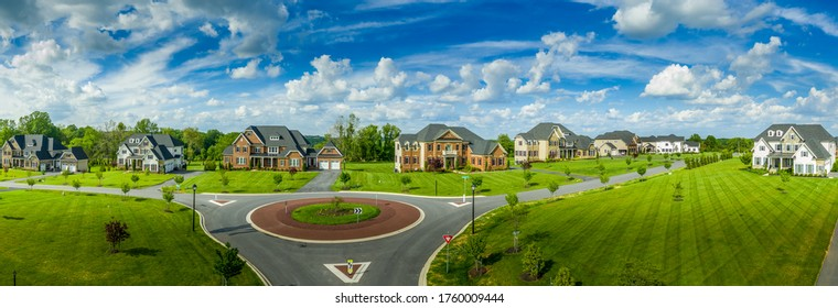 Aerial panorama of new neighborhood street with luxury real estate properties, mansions, brick covered villas with a roundabout and blue sky in Maryland USA