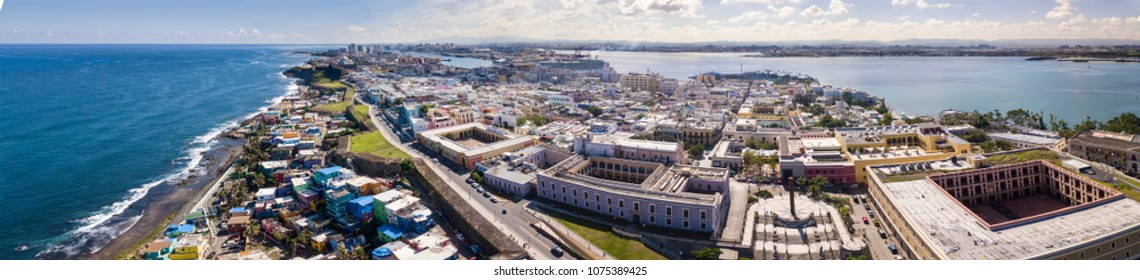 aerial panorama of Old San Juan, Puerto Rico with harbor in the background and La Perla Slum on bottom left.