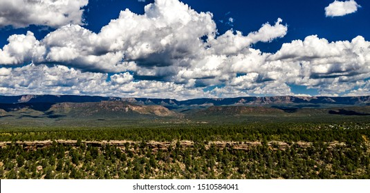 Aerial panorama over the Houston Mesa with the Mogollon Rim, cliffs, ridges, hills, mountains, blue sky with fluffy white clouds, green landscape on a beautiful sunny, summer day in Tonto Forest