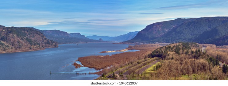 Aerial panorama over Rooster Rock State Park with shades of browns and grays and blues looking down the beautiful Columbia River Gorge on a Winter day with blue sky