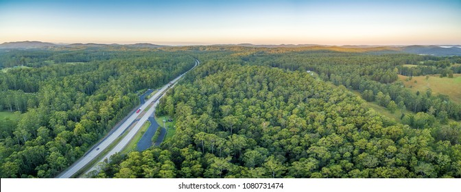 Aerial panorama of Pacific Highway and forests in rural area at sunset. NSW, Australia