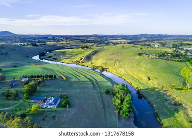 Aerial panorama of river flowing in beautiful Australian countryside at sunset. Yass, New South Wales, Australia