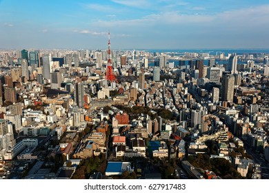 An aerial panorama from Roppongi over Downtown Tokyo, with landmark Tokyo Tower among crowded buildings, city streets crisscrossing the district & Tokyo Bay on distant horizon on a beautiful sunny day