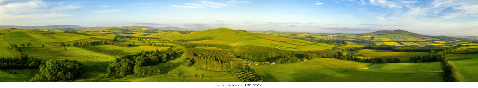 Aerial panorama of a Scottish Borders skyline showing Bonchester Hill, Ruberslaw and more with rolling hills, fields, trees and valleys below.