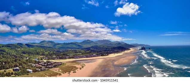 Aerial panorama shot at approximately 350 feet above Cannon Beach looking towards Haystack Rock with sand and surf and with mountains and clouds in the background on a blue sky day on the Oregon Coast