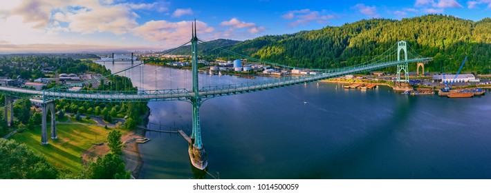 Aerial panorama of St Johns Bridge and Cathedral Park in early morning with blue skies and sunshine