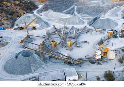 Aerial panorama of stone crushing and screening plant with stock pile, piles of sorted gravel and conveyor machinery