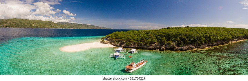 Aerial panorama of Sumilon Island off of Cebu, Philippines featuring a white sandy beach, local vacation boats, and tropical green ocean water.