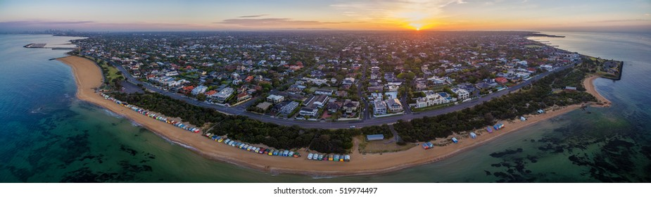 Aerial panorama of sunrise over Brighton suburb, showing iconic beach huts, houses, and the ocean. Melbourne, Victoria, Australia