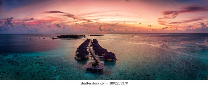 Aerial panorama of a tropical paradise island in the Maldives, Indian Ocea, with water lodges over the turquoise reef during sunset time