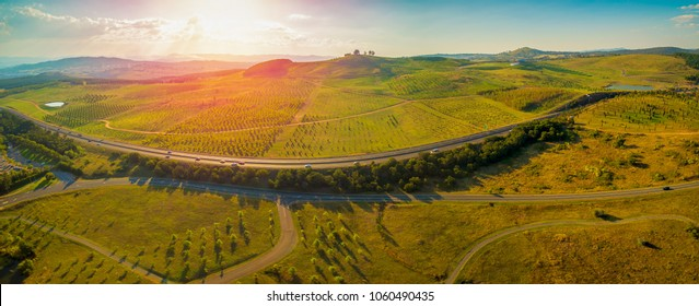 Aerial panorama of Tuggeranong Parkway and  National Arboretum at sunset in Canberra, Australia